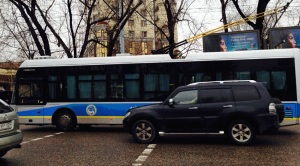 A Toyota Landcruiser Prado on front of a electric bus on a street in Almaty