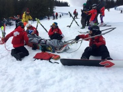 Ski patrollers on snowboards pulling a sled - I have not seen this before.